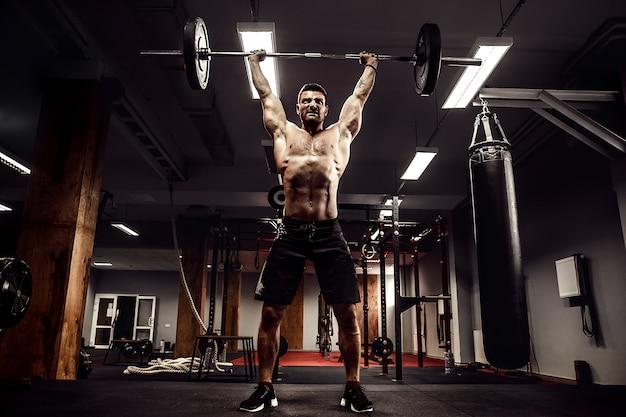 Muskularny mężczyzna fitness robi martwy ciąg sztangę nad głową w nowoczesnym centrum fitness