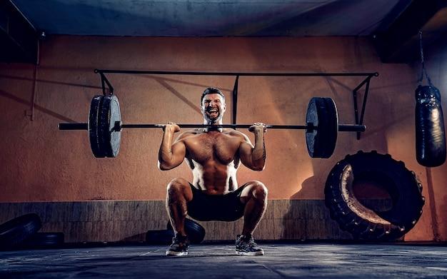Muskularny mężczyzna fitness robi wcisnąć sztangę nad głową w swoim garażu, samoizolacja. trening funkcjonalny. ćwiczenie na wyrywanie.