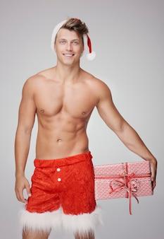 Muskularny mężczyzna i czerwony prezent na boże narodzenie