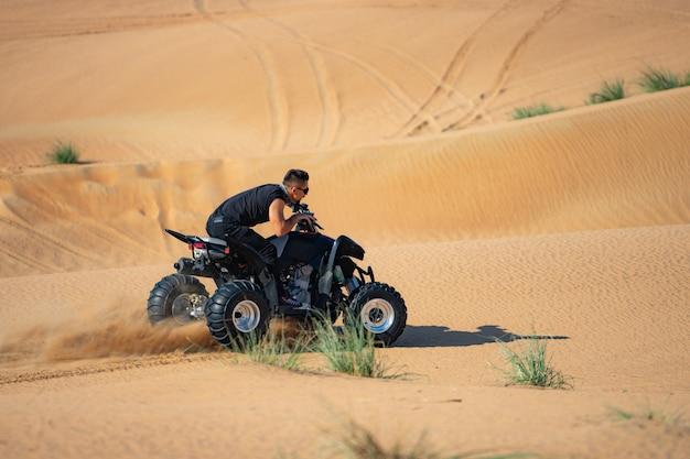 Muskularny mężczyzna jazda atv na pustyni.