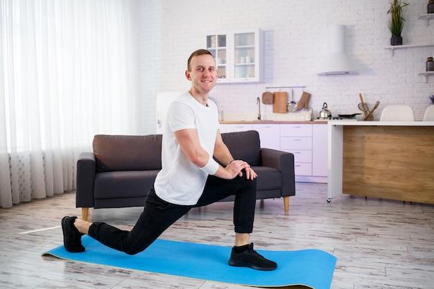 Muskularny mężczyzna lekkoatletycznego w t-shirt robi rozgrzewkowe ćwiczenia w domu. uprawianie sportu w domu w okresie kwarantanny. fitness poza siłownią