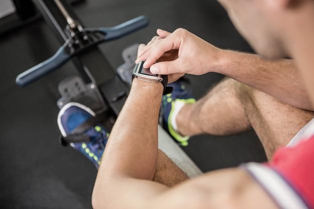 Muskularny mężczyzna na maszynę do wiosłowania za pomocą inteligentnego zegarka na siłowni