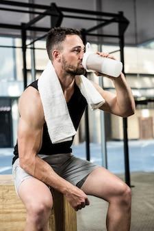 Muskularny mężczyzna pijący shake proteinowy w siłowni crossfit
