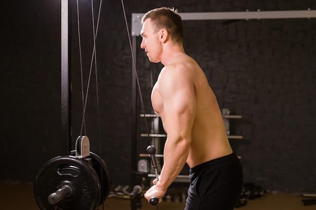 Muskularny mężczyzna, poćwiczyć w siłowni, ćwiczenia na triceps, silny mężczyzna abs nagi tułów