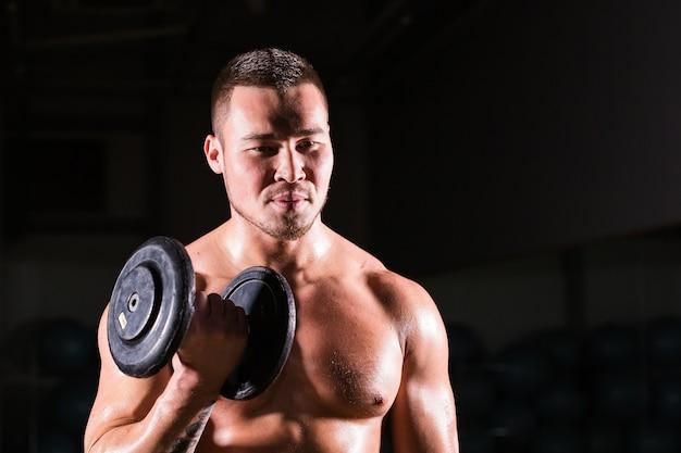 Muskularny mężczyzna, poćwiczyć w siłowni, ćwiczenia z hantlami na biceps, silny mężczyzna nagi tułów