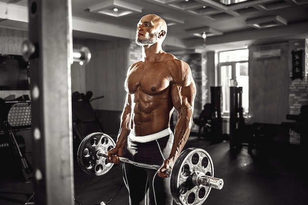 Muskularny mężczyzna, poćwiczyć w siłowni, ćwiczenia z hantlami