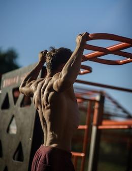 Muskularny mężczyzna podczas treningu na ulicy z poziomym paskiem.