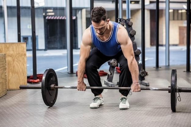 Muskularny mężczyzna podnoszenia sztangi na siłowni crossfit