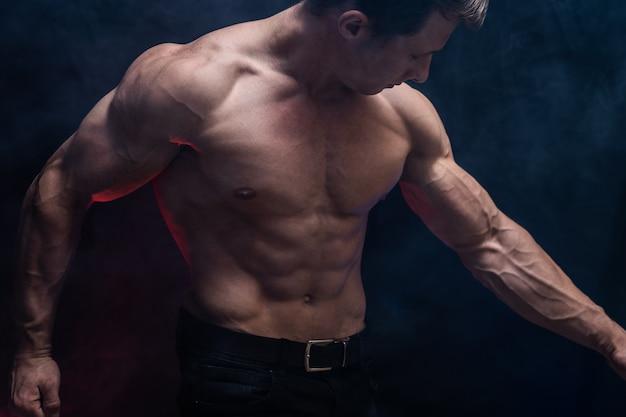 Muskularny mężczyzna pokazujący mięśnie na białym na czarnym tle z kolorowym dymem