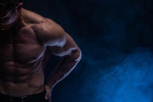 Muskularny mężczyzna pokazujący mięśnie na białym tle z kolorowym dymem. pojęcie zdrowego stylu życia.
