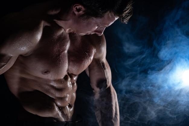 Muskularny mężczyzna pokazuje mięśnie na białym tle. pojęcie zdrowego stylu życia.