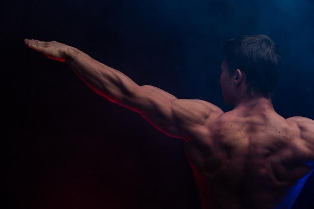 Muskularny mężczyzna pokazuje mięśnie na białym tle z bliska. pojęcie zdrowego stylu życia.