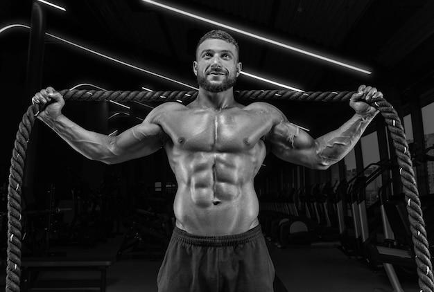 Muskularny mężczyzna pozowanie na siłowni z liną. koncepcja fitness.