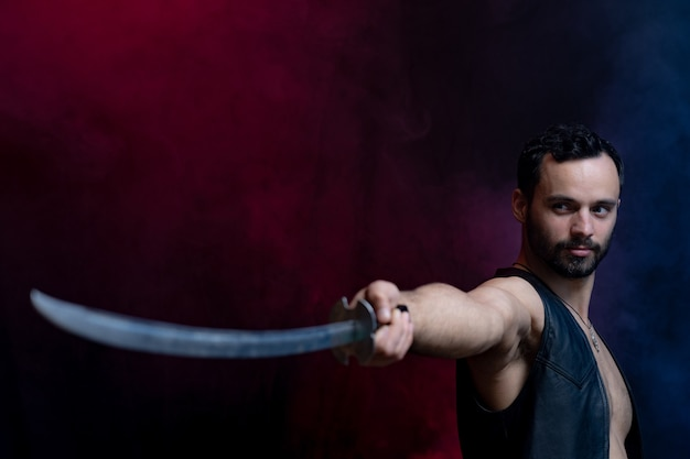 Muskularny mężczyzna pozowanie z długim mieczem na białym tle na tle czarne i wędzone