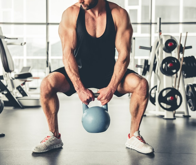 Muskularny mężczyzna pracuje z kettlebell w siłowni.