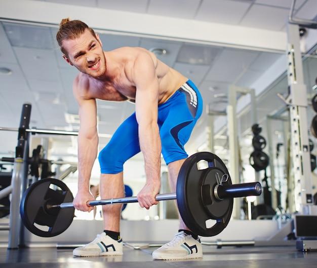 Muskularny mężczyzna robi ciężkich ćwiczeń
