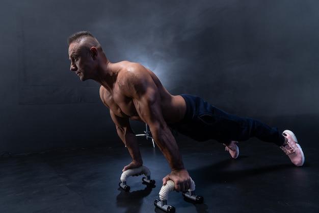 Muskularny mężczyzna robi ćwiczenia kalisteniczne na czarnym tle