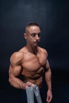 Muskularny mężczyzna robi ćwiczenia kalisteniczne z paskiem mocy na czarnym tle