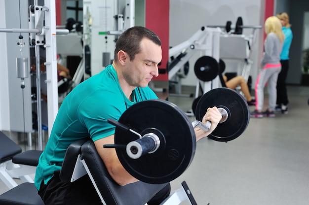 Muskularny mężczyzna robi ćwiczenia na biceps ze sztangą na ławce scotta