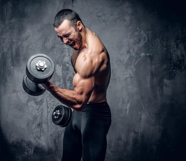 Muskularny mężczyzna robi ćwiczenia na biceps