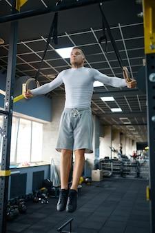 Muskularny mężczyzna robi ćwiczenia wytrzymałościowe na pierścieniach, trening fitness w siłowni