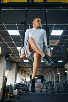 Muskularny mężczyzna robi ćwiczenia wytrzymałościowe na pierścieniach