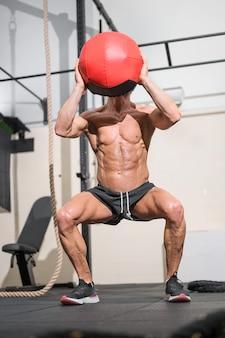Muskularny mężczyzna robi ćwiczenia z piłką lekarską w siłowni