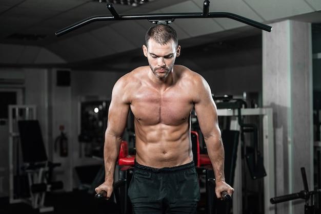 Muskularny mężczyzna robi pompki na nierównych barach w siłowni crossfit,