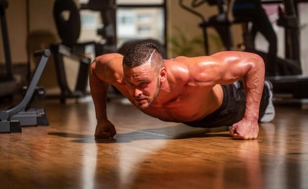 Muskularny mężczyzna robi pompki z jednej strony na tle siłowni.