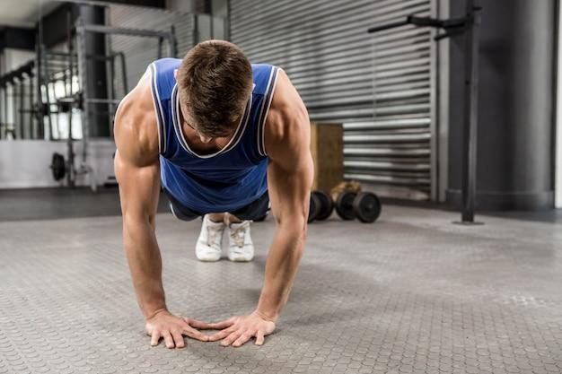 Muskularny mężczyzna robi push up na siłowni crossfit