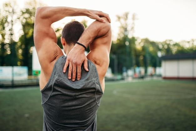 Muskularny mężczyzna sportowca robi ćwiczenia rozciągające, widok z tyłu, trening fitness. silny sportowiec w parku