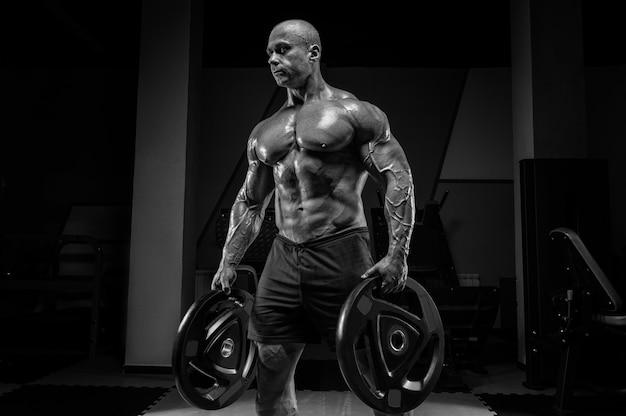 Muskularny mężczyzna stoi na siłowni ze sztangą. koncepcja kulturystyki i trójboju siłowego. różne środki przekazu