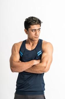 Muskularny mężczyzna stojący na sobie stroje gimnastyczne ze skrzyżowanymi rękami patrzeć w bok