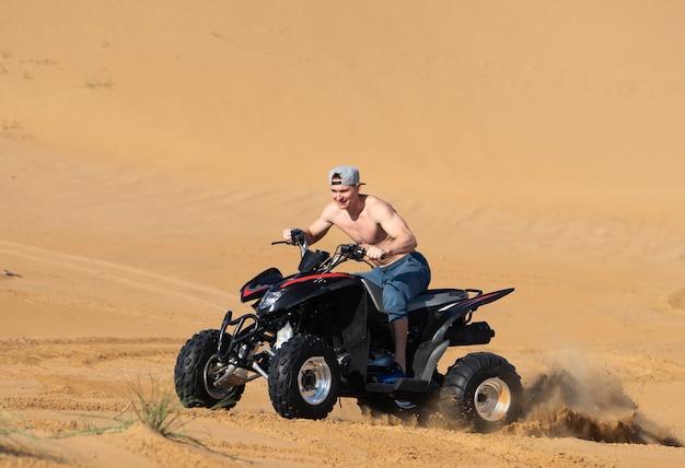 Muskularny mężczyzna topless jazda atv na pustyni.