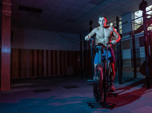 Muskularny mężczyzna trening na rowerze powietrznym w czerwono-niebieskim neonowym świetle. trening obwodowy