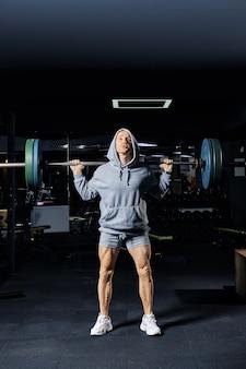 Muskularny mężczyzna treningu przysiady ze sztangą w siłowni