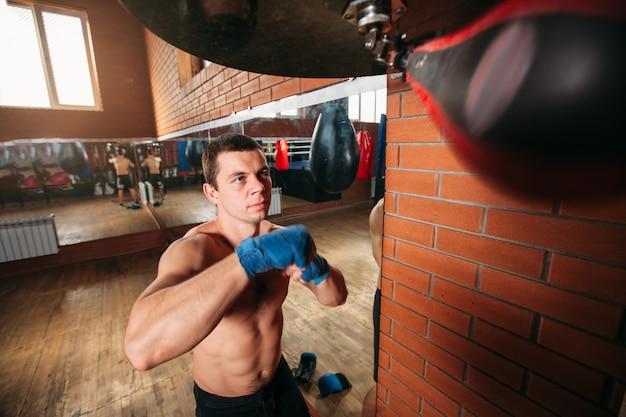 Muskularny mężczyzna trenuje z workiem treningowym.