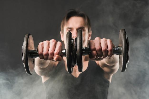 Muskularny mężczyzna trzyma ciężary