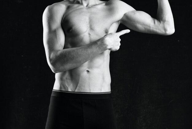 Muskularny mężczyzna w czarnych spodenkach siłownia czarno-białe zdjęcie