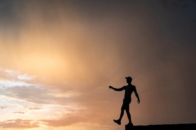 Muskularny mężczyzna wychodzi z krawędzi podczas dramatycznego zachodu słońca. koncepcja wyboru i odwagi.