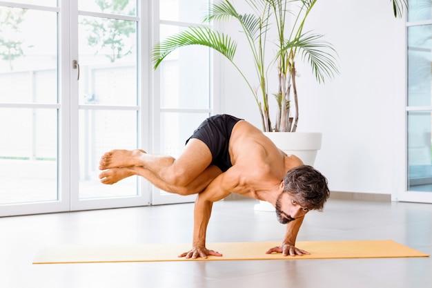 Muskularny mężczyzna wykonujący boczną pozę bakasana b