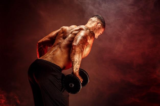 Muskularny mężczyzna z hantlami ćwiczeń. zdjęcie silnego mal