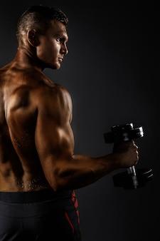 Muskularny mężczyzna z hantle. widok z boku. czarne tło