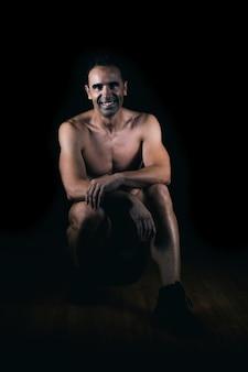 Muskularny mężczyzna z nagim torsem uśmiechający się do kamery