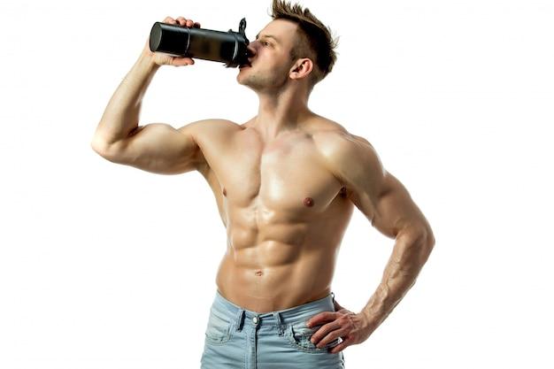 Muskularny mężczyzna z napojem proteinowym w shakerze