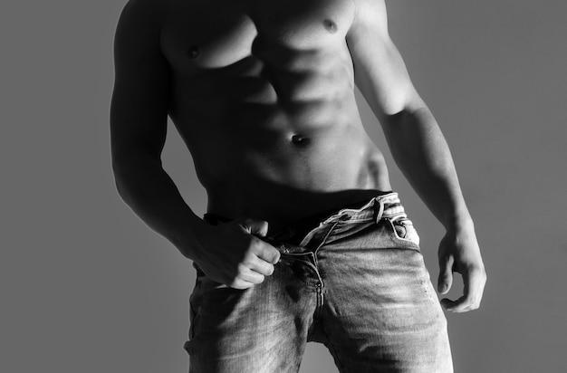 Muskularny mężczyzna z silnym nagim torsem pozuje z rozpiętymi dżinsami na szarej ścianie