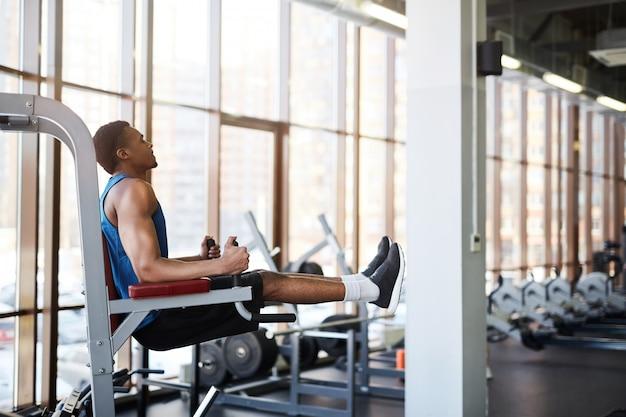 Muskularny mężczyzna za pomocą maszyn w siłowni