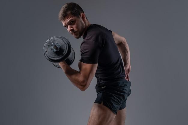Muskularny młody kulturysta robi uginanie bicepsa z hantlami