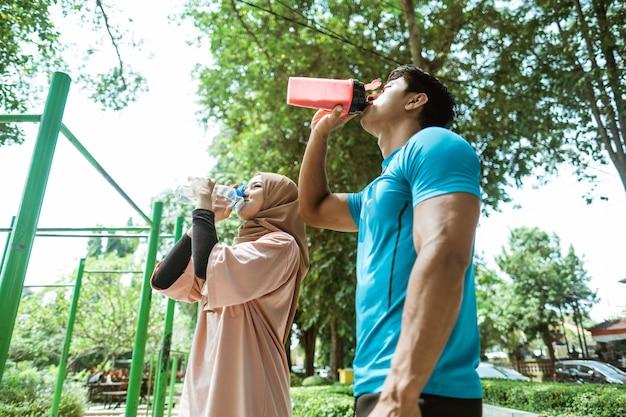 Muskularny młody mężczyzna i dziewczyna w chuście piją z pragnienia butelką podczas przerwy sportowej na świeżym powietrzu w parku