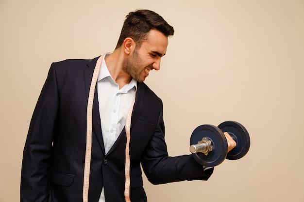 Muskularny pracownik biurowy mężczyzna trzyma hantle. opracowanie koncepcji biurowej.